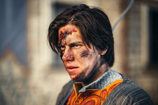 彼の肩に剣を持つ鎧の若い中世の戦士の肖像画。戦闘中、顔に傷がある