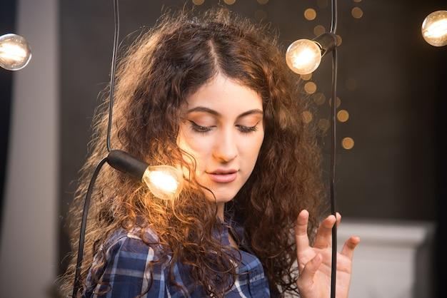 ランプの近くでポーズをとる格子縞のシャツの若いモデルの肖像画