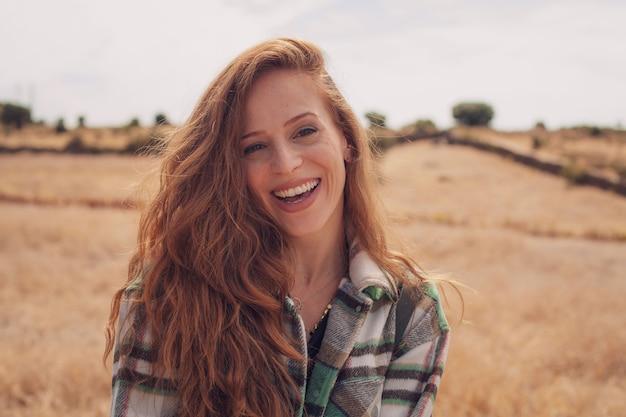彼女の背景にフィールドとカメラに微笑んでいる若いモデルの肖像画