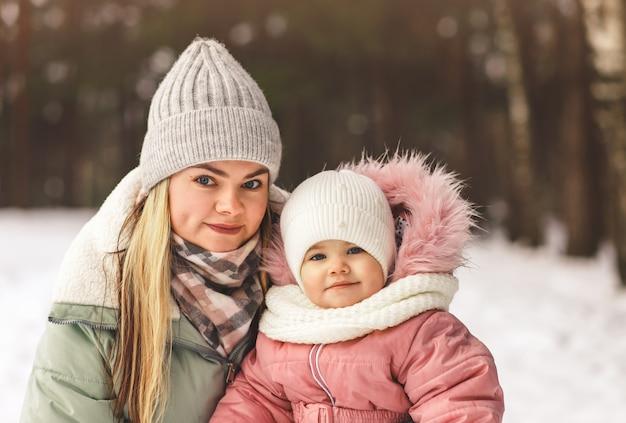森の中で冬の若い母と幼い娘の肖像画。カメラを見てください