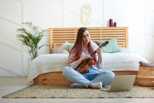 彼女の家の床に座ってウクレレを演奏している若いミュージシャンの肖像画、足を組んだ。リモート音楽トレーニング。