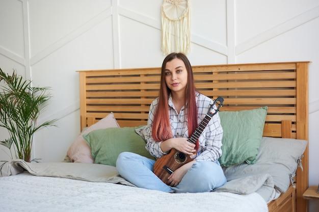 ウクレレを手にした若いミュージシャンの肖像画、女性は足を組んでベッドに座っています。