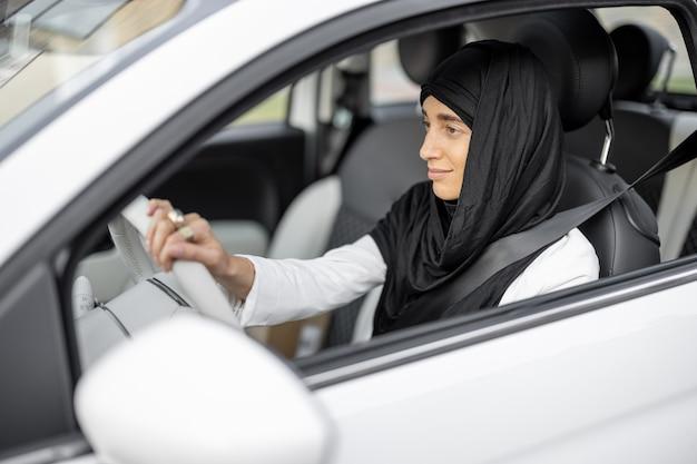 차를 운전하는 그녀의 머리에 히잡을 쓴 젊은 이슬람 사업가의 초상화. 이슬람 사회와 여성의 권리의 세계화와 현대화의 개념