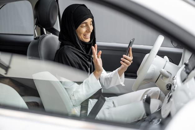 차를 운전하는 동안 전화로 히잡을 쓴 젊은 이슬람 사업가의 초상화. 이슬람 사회와 여성의 권리의 세계화와 현대화의 개념