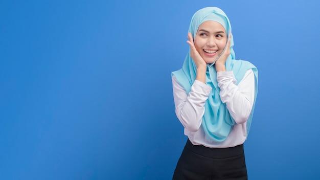 青い壁にヒジャーブと若いイスラム教徒の女性の肖像画
