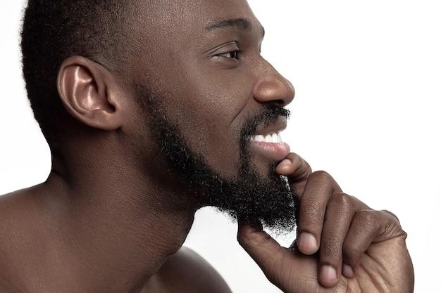스튜디오에서 젊은 벌 거 벗은 행복 미소 아프리카 남자의 초상화. 높은 패션 남성 모델 포즈와 흰색 배경에 고립