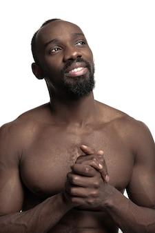 Портрет молодого голого счастливого улыбающегося африканца в студии.
