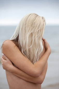 자연 배경에 젊은 벌거 벗은 여자의 초상화. 해변에서 아름 다운 젊은 금발 여자의 야외 초상화
