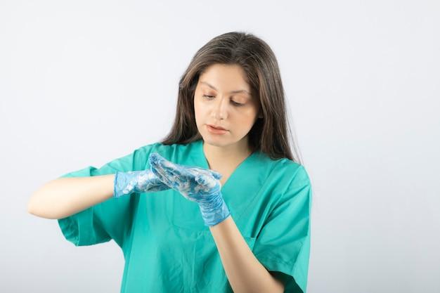 Портрет молодой медсестры или врача в зеленой униформе позирует.