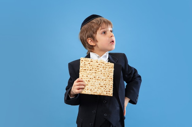 Портрет молодого православного еврейского мальчика, изолированного на синей студии
