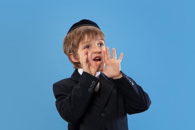 青いスタジオで隔離の若い正統派ユダヤ人の少年の肖像画