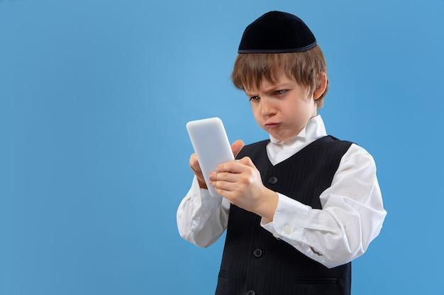 Портрет молодого ортодоксального еврейского мальчика изолированного на голубой студии