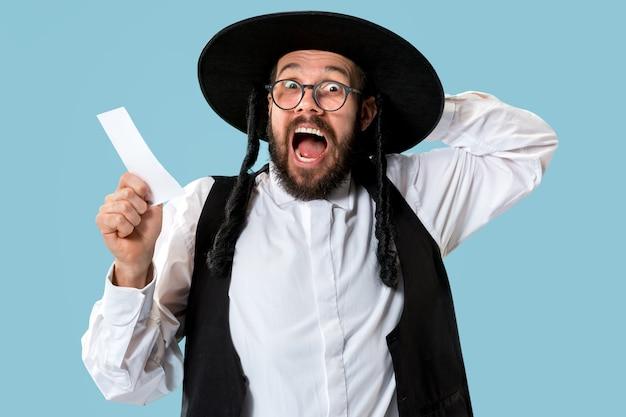 スタジオで賭けのスリップを持つ若い正統派ユダヤ人の肖像画。
