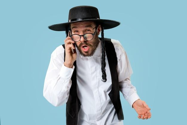 スタジオで携帯電話を持つ若い正統派ユダヤ人の肖像画。プリム、ビジネス、ビジネスマン、お祭り、休日、お祝い、ユダヤ教、宗教の概念。