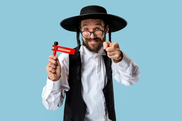 Портрет молодого ортодоксального еврея с деревянным храповым механизмом во время фестиваля пурим. праздник, праздник, иудаизм, традиции, концепция религии.