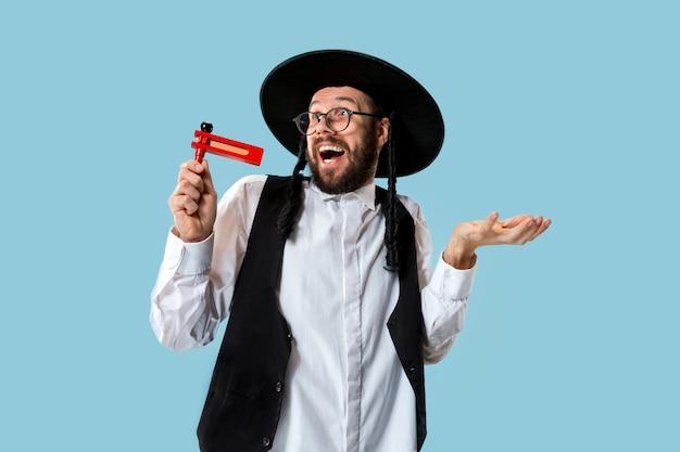 Портрет молодого ортодоксального еврея с деревянной трещоткой во время фестиваля пурим