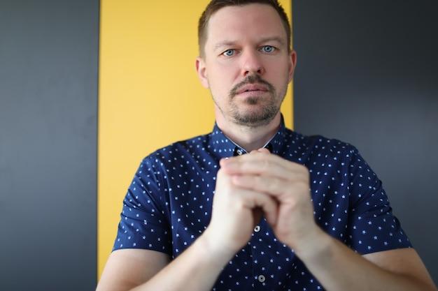 Портрет молодого молящегося в рубашке парень с щетиной сидит в задумчивой позе