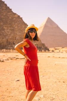 最大のピラミッドであるクフ王のピラミッドで赤いドレスを着た若い妊婦の肖像画。ギザのピラミッドは、世界最古の葬式の記念碑です。エジプト、カイロ市