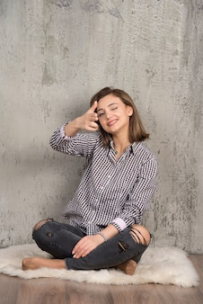 2本の指でカメラを指している格子縞のシャツを着た若いかわいい女の子の肖像画。