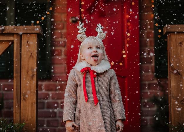 鹿のようなヘッドバンドと冬のコートを着た若いかわいい女の子の肖像画