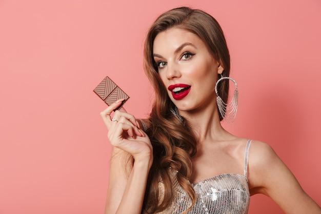 チョコレートを保持しているピンクの壁に分離された明るいスパンコールドレスの若いきれいな女性の肖像画。