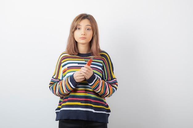 ボックスカッターを立って保持している若いきれいな女性モデルの肖像画。