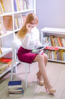 Портрет молодой красивой женщины, чтение в библиотеке