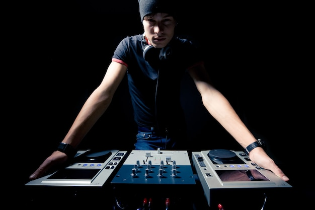 Портрет молодого профессионального ди-джея с клубом музыкального оборудования в темном освещении