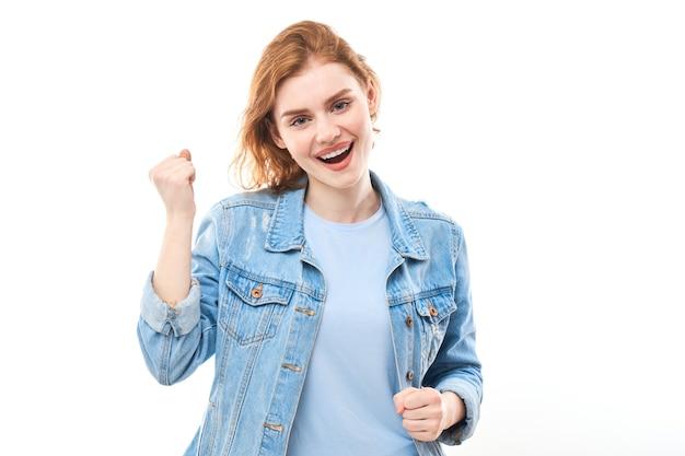 Портрет молодой рыжеволосой девушки на белом изолированном фоне в джинсах. смотрит в камеру, держась за руки перед собой в кулак