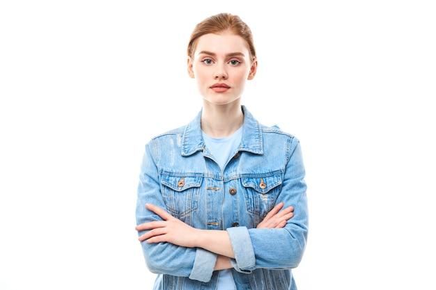 Портрет молодой рыжеволосой девушки на белом изолированном фоне в джинсах. смотрит в камеру