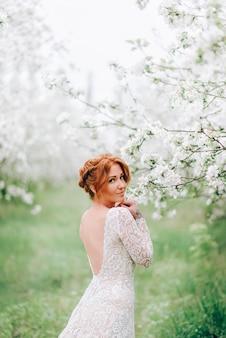 꽃이 만발한 사과 과수원에서 젊은 빨간 머리 여자의 초상화