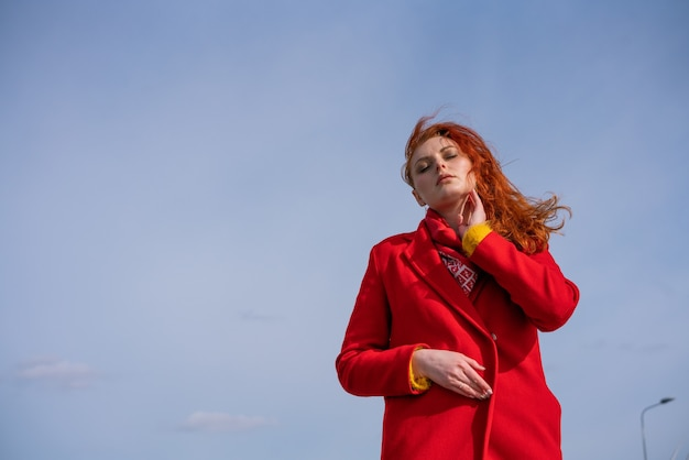 ボトムポイントのクローズアップから撮影した若い赤毛の大人の女性の肖像画は、女の子が立っています...