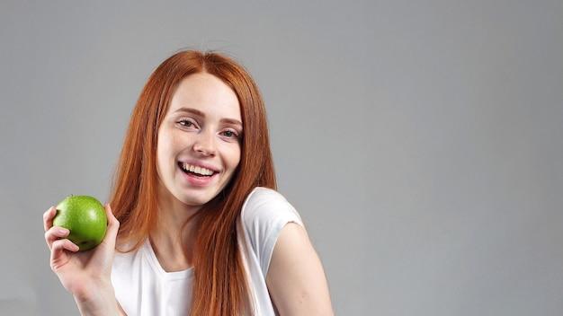 Портрет молодой рыжей девушки, держащей зеленое яблоко и улыбающейся