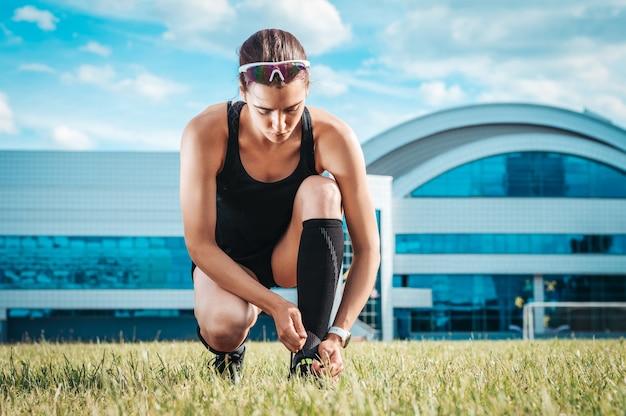 Портрет молодой бегуньи, которая зашнуровывает ботинки на футбольном стадионе. спортивная концепция.