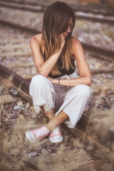철도 트랙에 잠겨있는 야외에 앉아 젊은 슬픈 여자의 초상화.