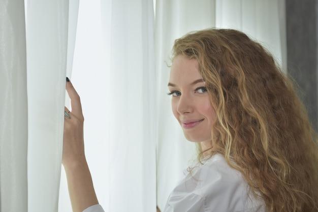 若いセクシーな美しく、幸せな女性の肖像画。ジェスチャーで女性の行為彼女が朝目を覚ますとき、