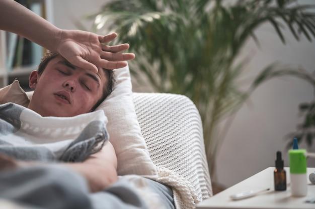 Портрет молодого больного парня лежа на софе и кладя его руку на его голову.