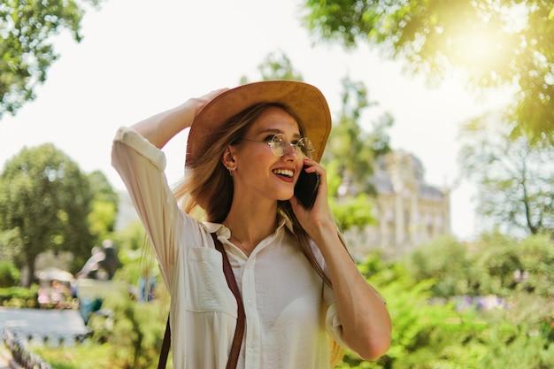 電話で話し、屋外で街を歩いている若いひたむきな金髪の女性の肖像画