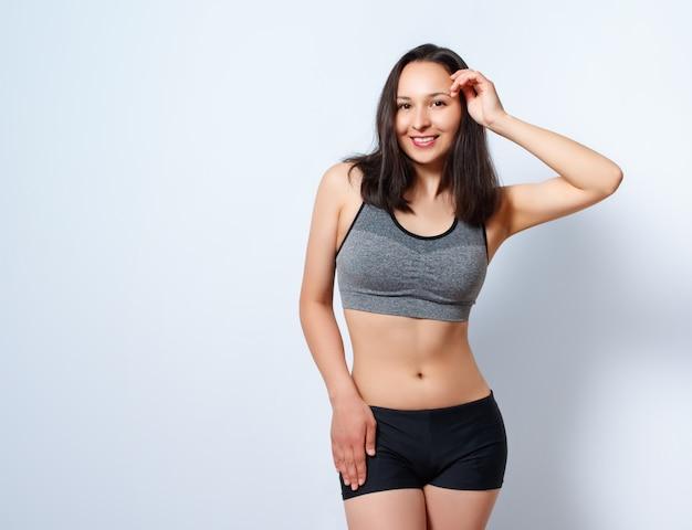 Портрет молодой стройной женщины фитнеса на белом фоне
