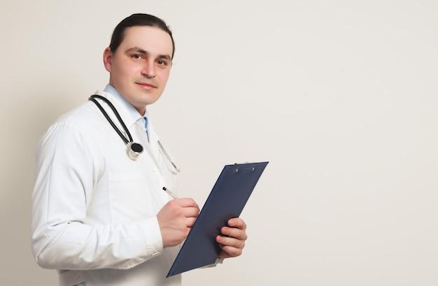 Портрет молодого улыбающегося доктора в халате, со стетоскопом и буфером обмена.