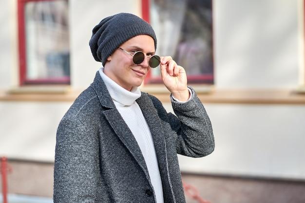 Портрет молодого улыбающегося привлекательного хипстерского человека в солнцезащитных очках, сером пальто, белом свитере и черных джинсах.