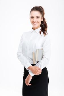 Портрет молодой улыбающейся деловой женщины, держащей книги, изолированные на белой стене