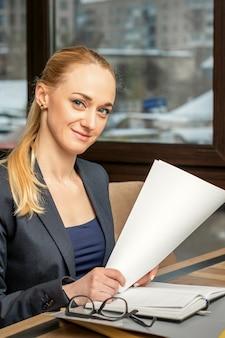Портрет молодой улыбающейся кавказской бизнес-леди готовит документы за столом в кафе