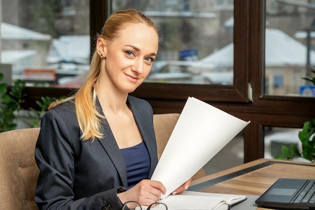 Портрет молодой улыбающейся кавказской бизнес-леди готовит документы с ноутбуком за столом в кафе