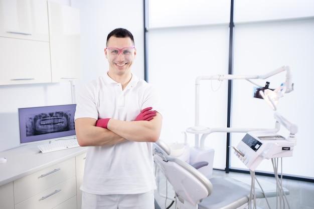 Портрет молодого улыбающегося дантиста в рабочих очках и в белой форме. мужчина скрестил руки и стоит у стоматологического кресла в кабинете.
