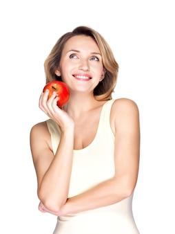 Портрет молодой улыбающейся здоровой женщины с красным яблоком, изолированным на белом.