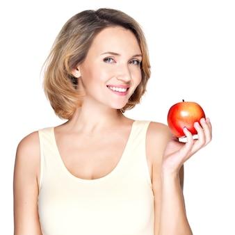 Портрет молодой улыбающейся здоровой женщины с красным яблоком - изолированным на белом.