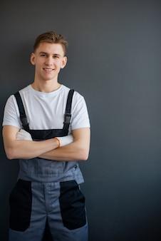 회색 바지와 흰색 티셔츠에 젊은, 웃 고, 전문 작업자의 초상화는 팔을 서 회색 배경에 넘어.