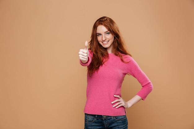 엄지 손가락을 찾고 젊은 웃는 빨간 머리 여자의 초상화