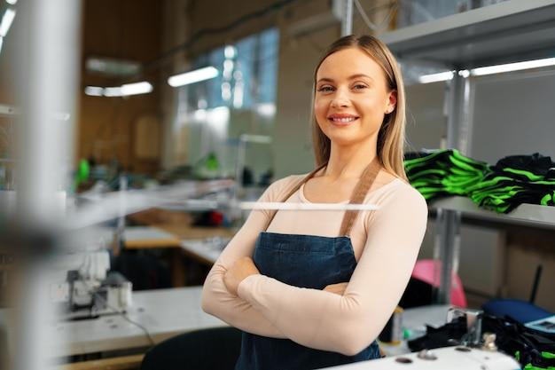 Портрет молодой улыбающейся швеи, стоящей на рабочем месте